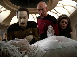 Data, Picard, and Troi stand over a frozen Torres