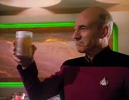 Picard holds out a beer to toast the room