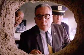 Image of the warden from Shawshank redemption looking down the tunnel