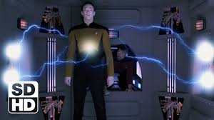 Data is electrocuted while Riker stands to look.