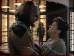 Worf and his mother embrace while Alexander is in the background.
