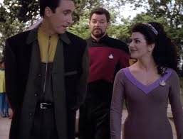 Conor and Troi talk while Riker walks behind them