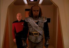 Worf in his Klingon gear preparing to leave the Enterprise, with Picard behindhim