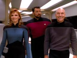 Picard and Crusher walking in front of Riker and brain sharing.
