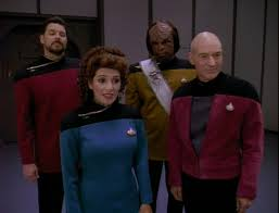 Riker, Worf, Troi, and Picard await the Ambassadors