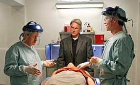 Ducky, Gibbs, and Palmer stand around a corpse in autopsy
