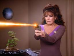 Troi shooting a phaser at Worf