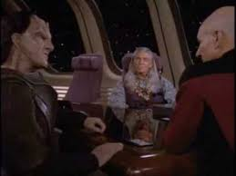 Picard and Gul Evek discuss their solution with the tribal leader