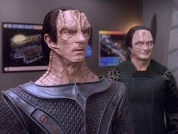Gul Dukat looking shocked while Garak looks on in the background mighty pleased with himself.