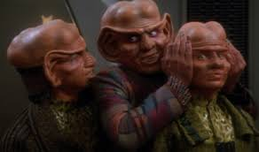 Rom sneering at Quark while he puts his hands over Pel's small lobes.