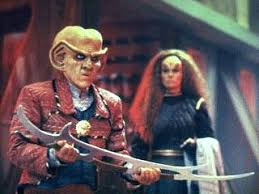 Quark holding a bat'leth and Brilka standing in the background.