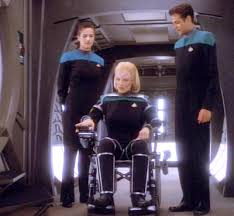 Melora in her chair surrounded by Bashir and Dax.