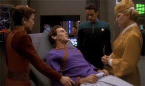Vedek Bareil in the infirmary surrounded by Kai Winn, Bashir, and Kira.