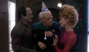 Garak and a woman holding up an age Bashir in a birthday hat