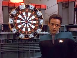 Bashir giving a sassy look in front of the dartboard