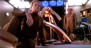 Odo sitting in the mess that is now his quarters and Quark standing in his pajamas