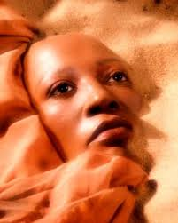 A black woman's face in the sand