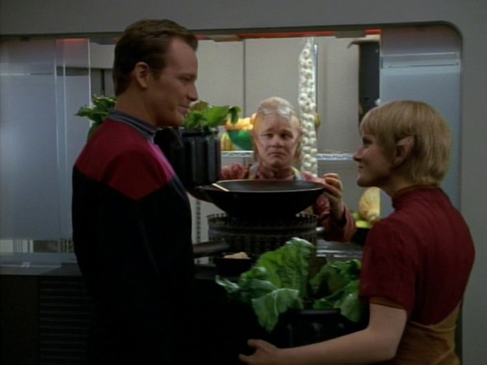 Neelix looking at Kes and Paris, while he has a SLEEVE of garlic bulbs behind him.