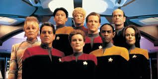 Neelix, Kim, Kes, Paris, EMH (back row). Chakotay, Janeway, Tuvok, Torres (front row)