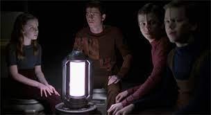 The Borg children around a light as Neelix tells the story