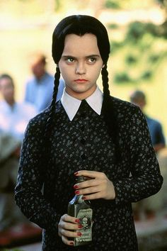 Wednesday Addams with her pigtails and black dress with white collar